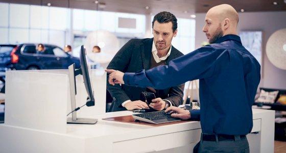 Zwei Personen stehen in einem Volvo Autohaus an einem Computerbildschirm, im Hintergrund ist ein Fahrzeug zu sehen