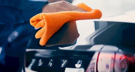Person poliert das Heck eines Volvo mit einem orangenen Mikrofasertuch
