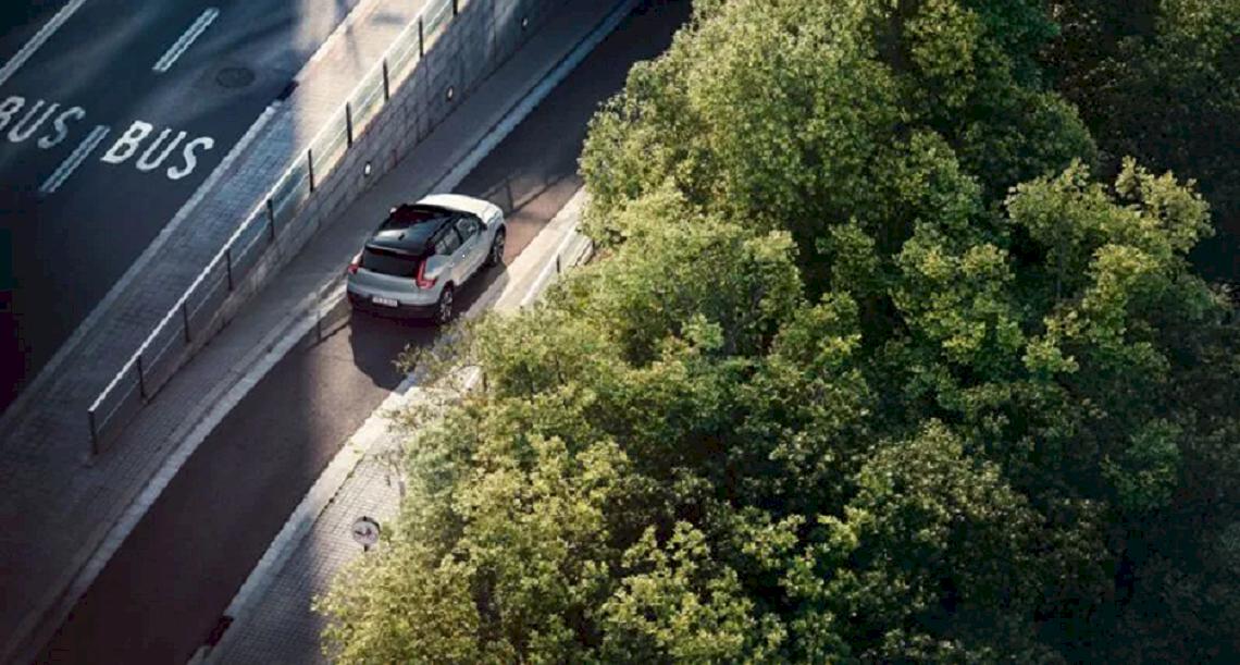 Volvo auf der Abfahrtstraße. Baume auf der Rechte Seite.