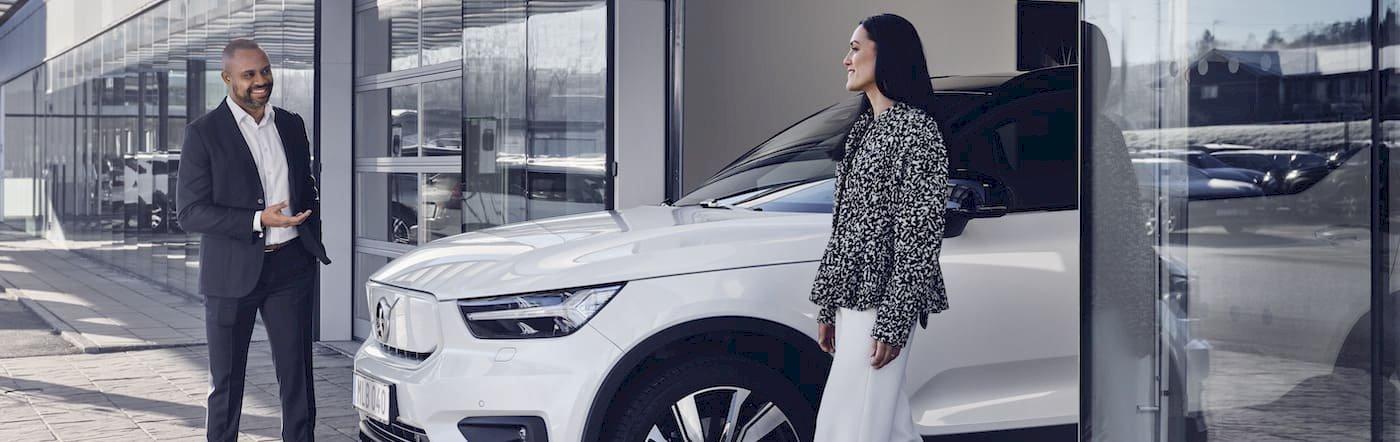 Zwei Menschen stehen an Autohaus um den Volvo XC40 Pure Electric