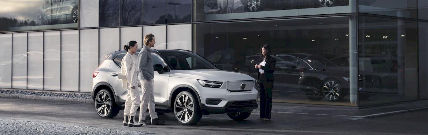 Drei Menschen stehen an Autohaus um den Volvo XC40 Pure Electric