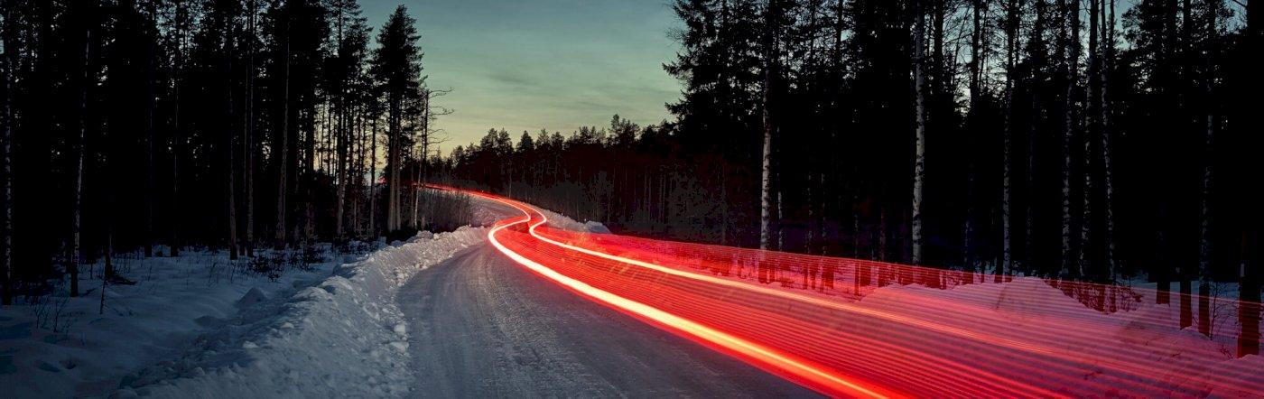 Roter Lichtstreifen, verursacht durch die Rücklichter eines Volvo zieht sich durch einen verschneiten Wald