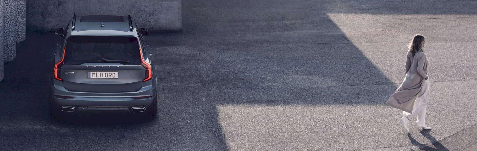Frau läuft weg von einem grauen Volvo.