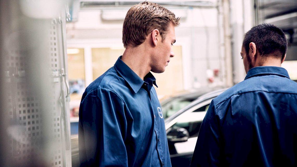 Zwei Mechaniker stehen in einer Werkstatt, im Hintergrund steht ein Volvo