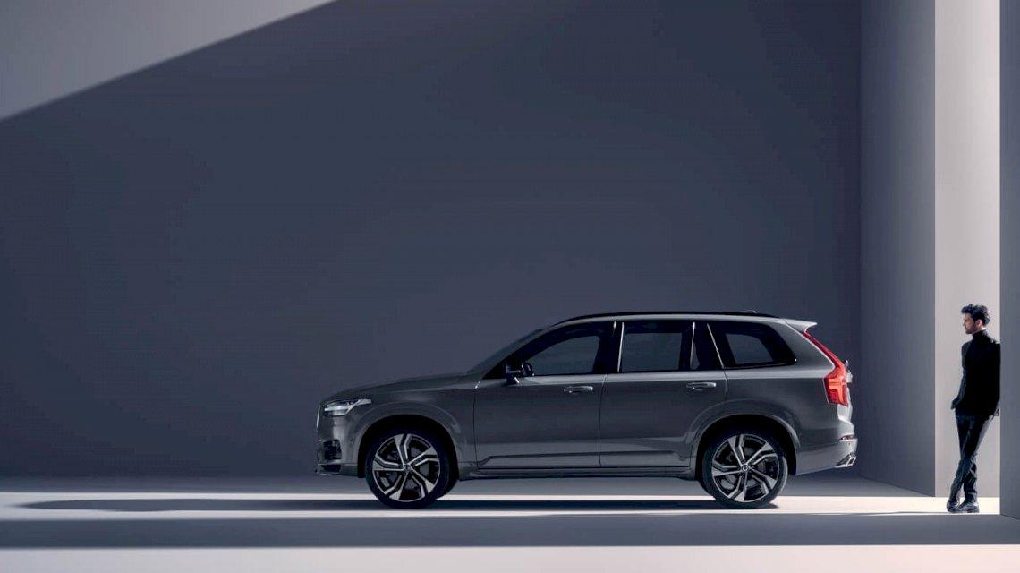 Volvo XC90 R-DESIGN Twin Engine in Thunder Grey steht in einem grauen Raum, hinter dem Fahrzeug steht eine Person, Licht fällt durch Säulen in den Raum - Seitenschuss