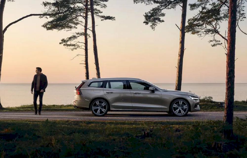 Grauer Volvo vor einer Meer Kulisse. Mann steht neben Volvo.