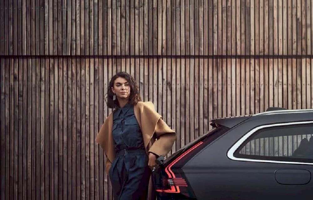 Frau vor einen schwarzen Volvo.