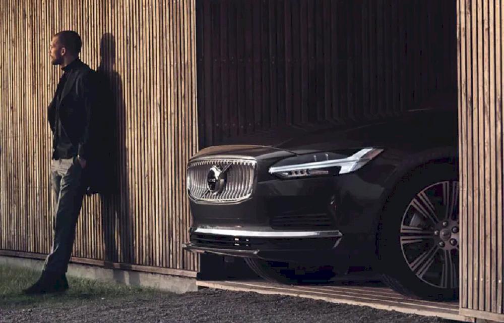 Mann vor einer Holzwand. Schwarzer Volvo guckt aus der Garage.